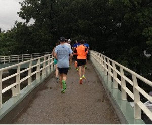 Group runners head over a footbridge to the Charles River.