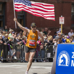 A patriotic runner holds the American flag while making the final turn at Boston 2014.